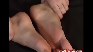 Cute timber gently playing with his feet and licking his toes